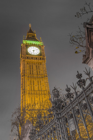 Big Ben at dramatic night with fence and tree branch silhouette, London, England photo