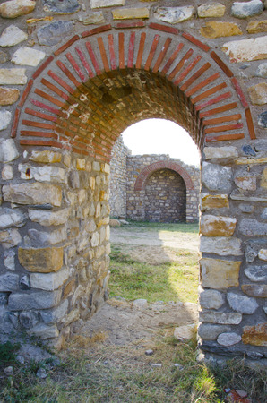 view of a wooden doorway: Old arched stone passage in the ancient town citadela ruins