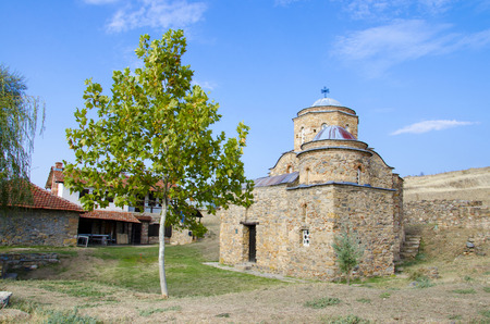 east gate: ancient church with green tree and blue sky. St  Nikola old church near ancient town ruins Bargala in Macedonia