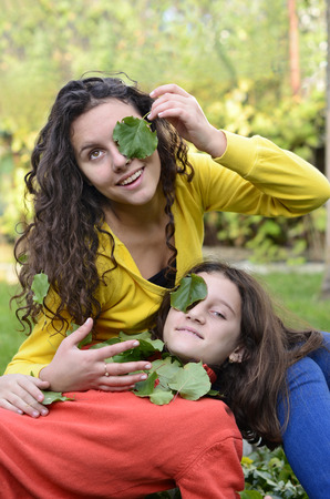 two beautiful teenager having fun playing in the garden with green leafs on their eyes photo