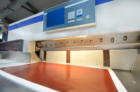 guillotine: Front view of a modern paper guillotine with touch screen used in commercial printing industry  industrial knife cutter