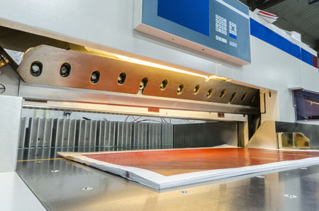 Front view of a modern paper guillotine with touch screen used in commercial printing industry  industrial knife cutter  photo