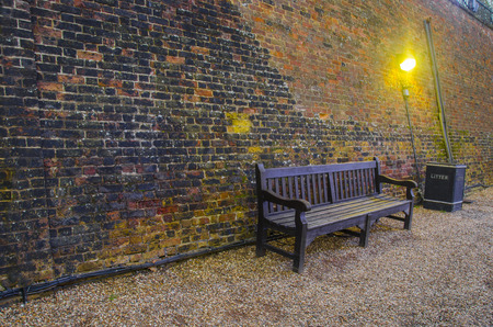 armrest: Old wooden benches in old alley with brick wall  Tower of London back street with litter bin Stock Photo