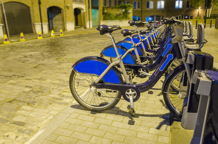 dependance: London City Bike Rental - Row of bikes for hire as part of a new scheme to encourage  pedal power  in the City of London.  The aim is to reduce dependance on cars and thereby reduce London Stock Photo