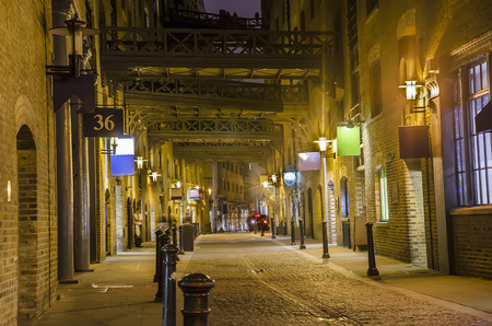 london people: dark alley - London traditional old stone paved road at night