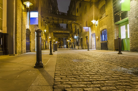 dark alley wide angle - London traditional old stone paved road at night photo