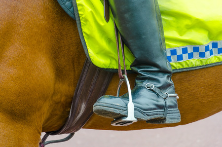 thug: Detail of boots of British policeman on horseback in London Stock Photo