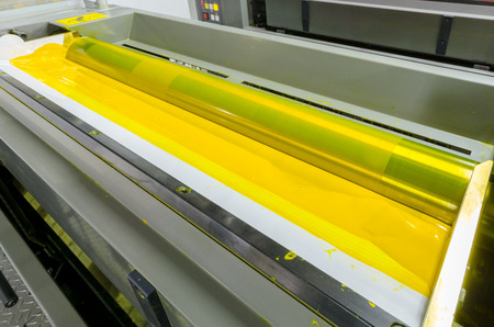 cian: print machine printing press rollers,Yellow color drum, dramatic light Stock Photo