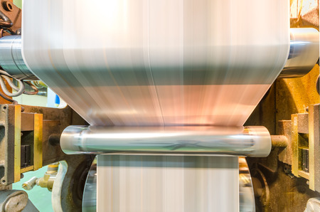 A large webset offset printing press running a long roll off paper over its rollers at high speed  Stock Photo