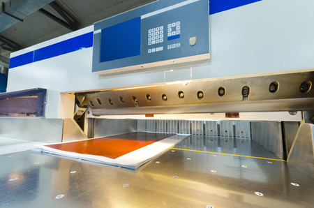 screen printing: Front view of a modern paper guillotine with touch screen used in commercial printing industry  industrial knife cutter