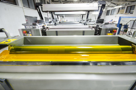 digital book: offset printing press machine rollers with yellow ink Stock Photo