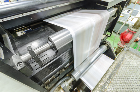 A large webset offset printing press running a long roll off paper over its rollers at high speed. Stock Photo