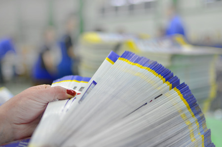 Manual controll and count of printed material packets with blur workers at background Zdjęcie Seryjne