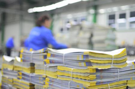 imprenta: Paquetes de materiales impresos con los trabajadores de desenfoque en el fondo