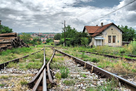 A view of the railway tracks leading with an old house station, dramatic sky photo