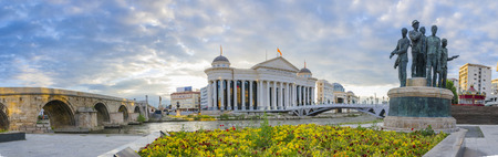 Amazing sunrise panorama of old stone bridge and archaeological museum of Macedonia with the monument of  gemidzii and river Vardar, bright colorful sky and spring flowers foregroung Publikacyjne