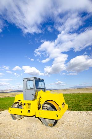 steamroller: Yellow Steamroller on highway asphalt construction site- Stock Image, against blue sky