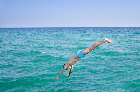 cliff jumping: Side view of a boy jump diving