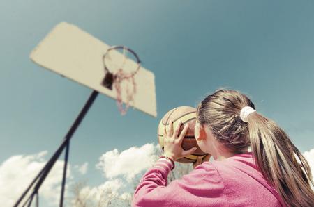 beautiful girl shooting basket and playing basketball, lower view wide angle Standard-Bild
