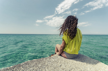 one girl only: Relaxing teenage girl. Curly hair young woman is enjoing calm ocean water surface and clear sky and horizon at bahamas.