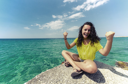 Young teen happy for successful holliday. Girl in yellow contrast shirt sitting at the edge and enjoying nice clean water and sky horizon.