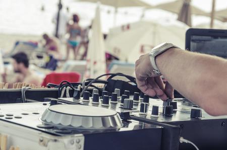 해변 Dj 근접입니다. 여름 해변 클럽 DJ가 일광욕을 즐기는 방문객들을 위해 파티를 즐겁게합니다.