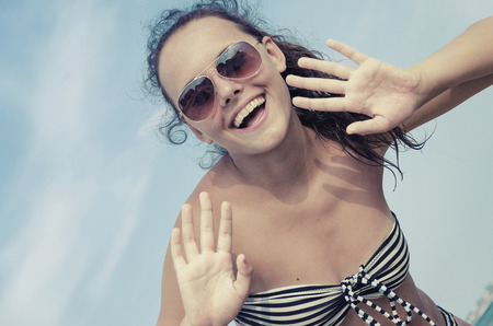teen girl bikini: Close-up of a young teen girl in bikini with glasess looking surprised against blue sky