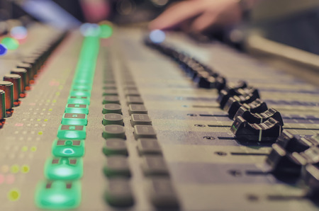 sound recording equipment: Blurred Hand on a mixer, operating the leader. Night concert scene. Wide angle, shallow deept of field Stock Photo