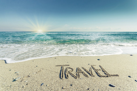 TRAVEL, creative abstract graphic message for your summer design. Inscription on wet sand word TRAVEL drawn on the sand of a beach at ocean horizon. Concept photo of summer vacation. photo