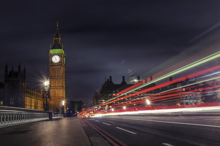 Big Ben and House of Parlament at dramatic night with light trails from vehicles on Westminister bridge, London, United Kingdom photo