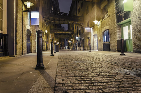 old street: dark alley wide angle - Stock Image. London traditional old stone paved road at night