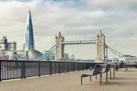 The Shard and Tower Bridge with an empty bench in London, UK photo