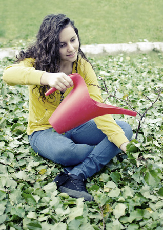 wet jeans: beautiful teenager yellow shirt girl water pouring small tree with red bucket Stock Photo