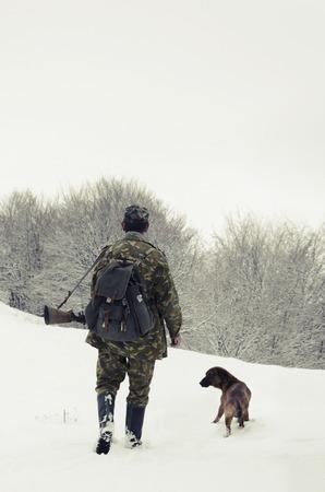 hombre disparando: Cazador masculino en ropa de camuflaje caminando en el campo de nieve con rifle de caza durante una cacería, perro lo sigue, tiempo brumoso