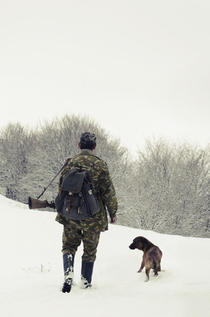 Male hunter in camouflage clothes walking on the snow field with hunting rifle during a hunt, dog follows him, foggy weather photo