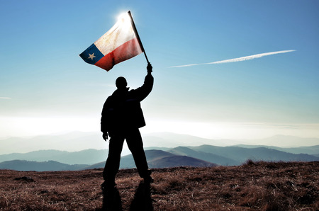 bandera chilena: exitoso ganador silueta del hombre que agita la bandera de Chile en la cima del pico de la montaña