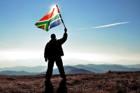 山のピークの上に南アフリカ共和国の旗を振って成功したシルエット人勝者