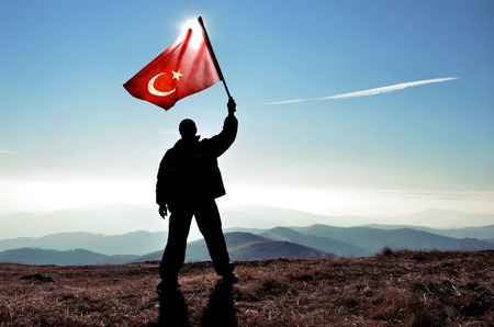 successfull silhouette man winner waving Turkish flag on top of the mountain peak Stock Photo