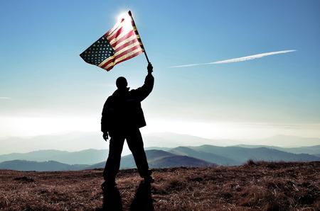 successfull silhouette man winner waving American flag on top of the mountain peak photo