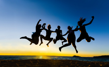 Summer party people jumping for joy, fun at vibrant sunset sky Banque d'images