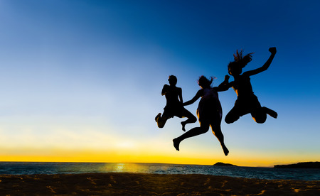 friends and family: silhouette of friends jumping in sunset