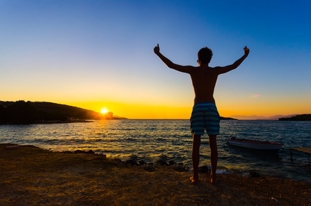 elated: Happy celebrating winning success man at sunset or sunrise standing elated with arms raised up above his head celebratiing of having reached summit goal