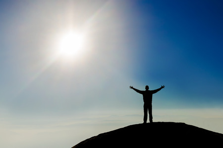 top of the world: Silhouette of successful man and beautiful sky on the top of the world Stock Photo