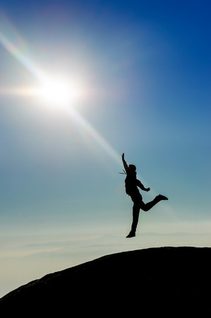 top of the world: HEAVEN. Man Silhouette jumping reaching the sun at the top of the world. High mountain range Stock Photo