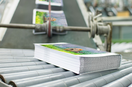 Book, magazine,  production line into press plant house. Automatic assembly line close up