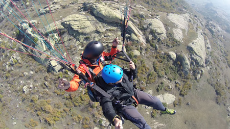 skydive: Tandem paragliding over rocky mountains Stock Photo