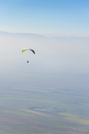 skydive: Alone paraglider fly over valley aerial pov vertical composition