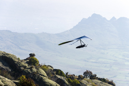 adrenaline: Glider silhouette take off high mountain rock. Extreme adrenaline sport fly