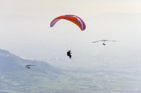 adrenaline: paraglider and two gliders do extreme adrenaline sport flight. Aerial pov