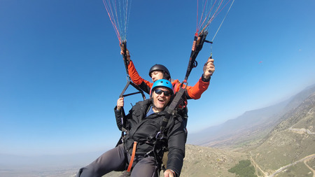 Tourist playing paragliding guided by a pilot